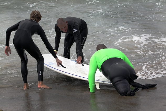Two surf instructors assist Cpl. Toran Gaal, a double amputee, onto his surfboard to catch another wave during the Operation Amped surf clinic at San Onofre beach here, Aug. 24. During the three days, veterans are paired with a surf instructor to teach them the fundamentals of surfing.