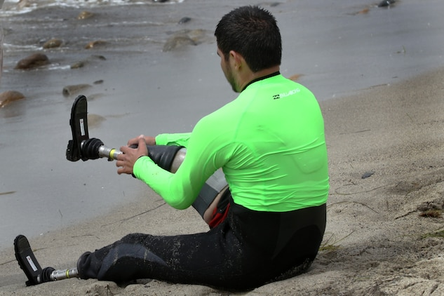 Cpl. Carlos Torres, a double amputee, puts on his legs before going out into the water to ride a few waves at the Operation Amped surf clinic at San Onofre beach here Aug. 24. The disabilities of the veterans range from traumatic brain injury  to amputations to post traumatic stress disorder.