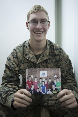 Lance Cpl. Gregg J. Schaefer, a landing support specialist with Combat Logistics Battalion 31, 31st Marine Expeditionary Unit, holds a picture of himself with his 11 brothers and sisters here, Aug. 21. With his siblings serving as the motivation to change his ways, Schaeffer transformed himself from troublemaker to role model by becoming a Marine. The 31st MEU is the Marine Corps' force in readiness in the Asia-Pacific region and the only continuously forward deployed MEU.