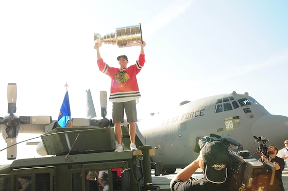 Chicago Blackhawks right wing Patrick Kane holds up the Stanley cup in front of the C-130 aircraft just before entering the hangar to greet members of the military at the Niagara Falls Air Reserve Station on Aug. 24, 2013 (Air National Guard Photo/ Senior Master Sgt. Ray Lloyd)