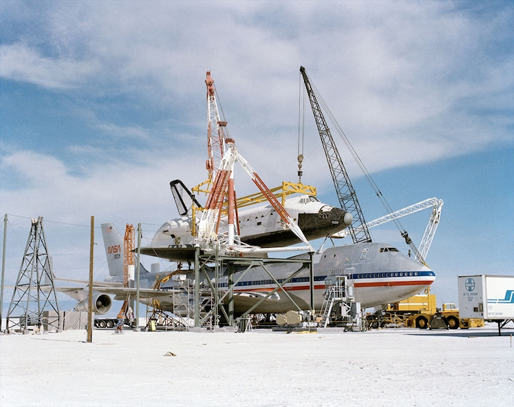 The Space Shuttle Columbia is hoisted into place by cranes at White Sands Northrup Strip. Columbia made the first, and only, shuttle landing at the New Mexico facility in March 1982 during STS-3. The shuttle was flown by Astronaut C. Gordon Fullerton, who passed away Wednesday, Aug. 21, at the age of 76. The fine gypsum sand battered the spacecraft so harshly that despite a deep cleaning and years of use, the sand was still found on subsequent missions.