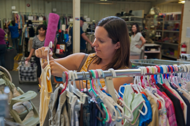 Carrie, wife of Maj. James, 6th Reconnaissance Squadron pilot, checks out baby clothes as other members of Team Holloman shop during the newly reopened Thrift Shop at Holloman Air Force Base, N.M., Aug. 20. The Thrift Shop provides members of Team Holloman a means of acquiring new and gently-used goods at a portion of the cost of the item's retail value. Last name withheld due to operational safety constraints. (U.S. Air Force photo by Airman 1st Class Aaron Montoya/Released)