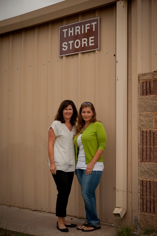 Tracy Patton, wife of Lt. Col. Jeff Patton, 9th Attack Squadron commander, and Carrie, wife of Maj. James, 6th Reconnaissance Squadron pilot, pose prior to opening the Thrift Shop for the 2013 summer season at Holloman Air Force Base, N.M., Aug. 20. The Thrift Shop provides members of Team Holloman a means of acquiring new and gently-used goods at a portion of the cost of the item's retail value. Last name withheld due to operational safety constraints. (U.S. Air Force photo by Airman 1st Class Aaron Montoya/Released)