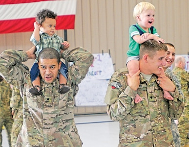 Children play with CAB Soldiers prior to an Aug. 15 deployment ceremony for the CAB at Marshall Army Airfield.  Photo by: J. Parker Roberts, 1ST INF. DIV.