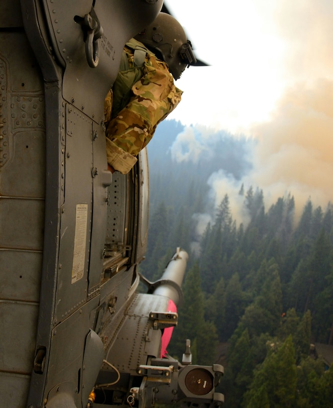 California Air National Guardsmen from the 129th Rescue Wing perform precision water bucket drops in support of the Rim Fire suppression operation at Tuolumne County near Yosemite, Calif., Aug. 26, 2013.  (Courtesy photo by Staff Sgt. Ed Drew)