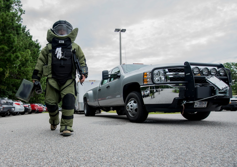 Staff Sgt. Aaron Clark, 628th Civil Engineer Squadron explosive ordnance disposal technician, walks toward the simulated suspect device with his bomb suit and equipment to examine the device further during an anti-terrorism exercise on Aug. 22, 2013, at Joint Base Charleston - Weapons Station.  The scenario was one of many that tested JB Charleston to perform their duties under heightened security conditions during a routine security exercise. (U.S. Air Force photo/Tech. Sgt. Rasheen Douglas)