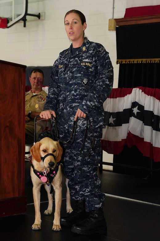 Chief Petty Officer Jeannette Tarqueno, a gunner's mate and wounded warrior, addresses the audience with her new service dog Gaza, during a ceremony Aug. 26, 2013, at the Naval Consolidated Brig Charleston, S.C. Gaza was trained by NCBC prisoners in conjunction with Carolina Canines for Service, a non-profit organization that trains service dogs for veterans with disabilities. Gaza, a Labrador retriever, will assist Tarqueno by providing more independence and comfort in her life. (U.S. Air Force photo/ Airman 1st Class Chacarra Neal)