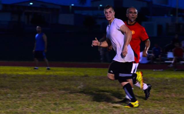 Senior Airman Reid Martinak, 36th Civil Engineer Squadron, runs past a defender from the 36th Medical Group during the intramural soccer championship game on Andersen Air Force Base, Guam, Aug. 26, 2013. The 36th MDG won the game 2-1 and became this year's soccer champions, finishing the season with an 8:0 win-loss record. (U.S. Air Force photo by Airman 1st Class Mariah Haddenham/Released)