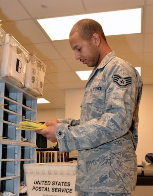 Staff Sgt. Brandon Gordon, 36th Communications Squadron postal clerk, distributes package notification slips to customers' mailboxes on Andersen Air Force Base, Guam, Aug. 26, 2013. The five Airmen who make up the military postal section of the Andersen Post Office sort through approximately 5,000 pounds of mail each month, with a large amount of that going to the dorm residents. (U.S. Air Force photo by Airman 1st Class Mariah Haddenham/Released)