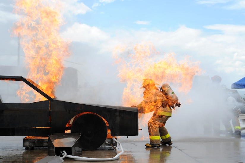 Senior Airman Christopher Crusius, a 612th Air Base Squadron firefighter, is engulfed in flames as he opens the hood during a car fire here as part of Central America Sharing Mutual Operational Knowledge and Experiences (CENTAM Smoke) Exercise Aug 27, 2013. JTF-Bravo firefighters will train alongside Hondurans, Belizeans, Costa Ricans, Guatemalans, El Salvadorans, Panamanians and Nicaraguans partner nation firefighters allowing the U.S. and Central America firefighters four days of team-building exercises.(Photograph released by U.S. Air Force Staff Sgt. Jarrod Chavana)