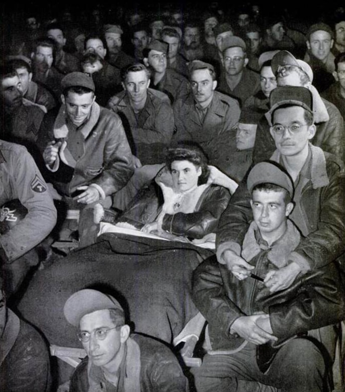 """Yvette Hamel takes in some entertainment with the men of the 371st Fighter Group at an airfield in France.  This photograph was published on page 45 of the November 27, 1944, issue of LIFE Magazine.  The caption for this photo was:   """"LEGLESS YVETTE HAMEL, DRESSED IN A FLYING JACKET AND BLOUSE MADE OF PARACHUTE SILK, WATCHED A GI SHOW WITH MEN OF THE FIGHTER GROUP WHICH ADOPTED HER.""""  The short article beneath LIFE's photo included the following details of Yvette's remarkable story:  AIRMEN'S WARD U.S. fliers in France adopt girl who lost both legs in Normandy  Last July 16-year old Yvette Hamel was milking a cow in a field near the Norman town of La Haye du Puits.  A German shell landed in the field, wounding her so badly that both of her legs had to be amputated.  A few days later, Colonel Bingham Kleine, commanding officer of a 9th AF fighter group, met her in a near-by hospital.  Colonel Kleine saw that she was moved to a better hospital, finally arranged to have her treated in his group dispensary.  When the group moved, Yvette moved with it, cared for by several hundred men and two French Red Cross volunteers.  The men of Colonel Kleine's group are taking fine care of Yvette. Among themselves they have raised more than $2,000 for new hospital bills and have spared no trouble to keep her comfortable.  In the midst of all this attention Yvette is cheerful, although she cries a little when she thinks no one is around.  She doesn't speak much English but is learning the curious GI brand as quickly as anyone. (LIFE Magazine)"""