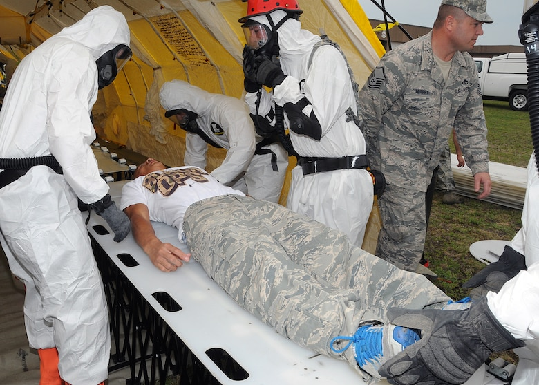Members of the 143d Airlift Wing involved in the Region 1 Chemical, Biological, Radiological, Nuclear, High Yield Explosive Enhanced Response Force Package (CERFP) perform a training exercise to demonstrate the team's responsibilities and capabilities to potential new members and leadership. A member of the RIANG Student Flight (on stretcher) volunteered to play a victim for the exercise. The Region 1 CERFP is made up of members of the Air and Army National Guard from Maine, New Hampshire, and Rhode Island. National Guard Photo by Master Sgt Janeen Miller (RELEASED)