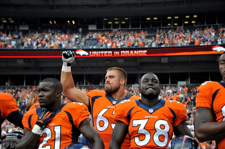 Air National Guard 1st Lt. Benjamin Garland (63), Denver Broncos Offensive Guard and 140th Wing Public Affairs Officer, stands with Ronnie Hillman (21) and Montee Ball (38) as he pumps his fist in the air after the National Anthem at Sports Authority Field at Mile High Stadium, Denver, Colo. Aug 24, 2013. Garland, who originally entered the National Football League in 2010 after graduating from the U.S. Air Force Academy, was on the Bronco's reserve/military list while fulfilling his active duty obligations in the Air Force. In 2012 Garland joined the Colorado Air National Guard and made the Broncos practice squad as a defensive lineman and is competing this season to make the 53 man final roster. (Air National Guard photo by Tech. Sgt. Wolfram M. Stumpf)