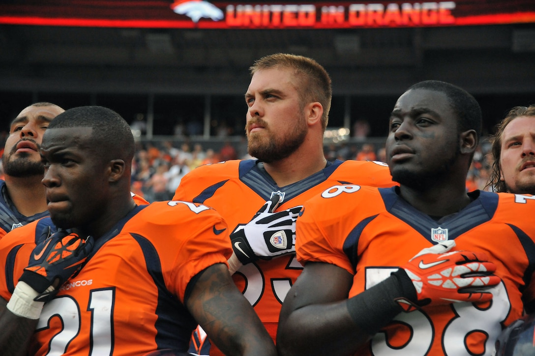 Air National Guard 1st Lt. Benjamin Garland, Denver Broncos Offensive Guard and 140th Wing Public Affairs Officer, stands with Ronnie Hillman (21) and Montee Ball (38) as he listens to the National Anthem at Sports Authority Field at Mile High Stadium, Denver, Colo. Aug 24, 2013. Garland, who originally entered the National Football League in 2010 after graduating from the U.S. Air Force Academy, was on the Bronco's reserve/military list while fulfilling his active duty obligations in the Air Force. In 2012 Garland joined the Colorado Air National Guard and made the Broncos practice squad as a defensive lineman and is competing this season to make the 53 man final roster. (Air National Guard photo by Tech. Sgt. Wolfram M. Stumpf)