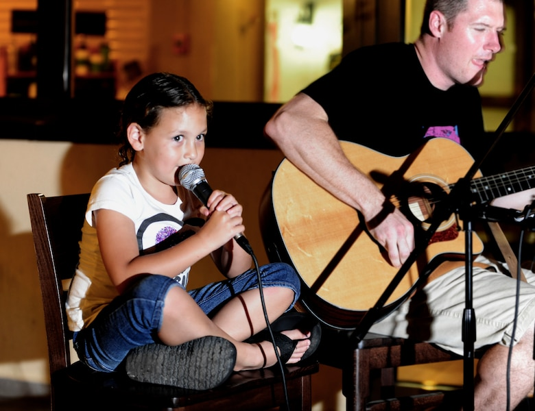 Staff Sgt. Michael Buchanan, 39th Medical Operations Squadron mental health technician, and his daughter duet during open mic night Aug. 13, 2013, at Incirlik Air Base, Turkey. Open mic night provides Team Incirlik members to show case their various talents and happens every Tuesday. (U.S. Air Force photo by Senior Airman Daniel Phelps/Released)
