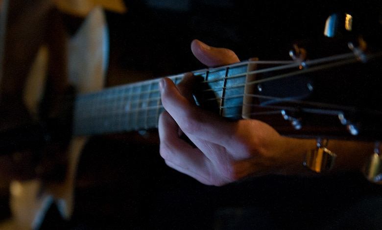 Fingers glide across the fret board of a guitar during open mic night Aug. 6, 2013, at Incirlik Air Base, Turkey. Open mic occurs outside the Incirlik club complex and allows Team Incirlik members to showcase various talents. (U.S. Air Force photo by Senior Airman Daniel Phelps/Released)