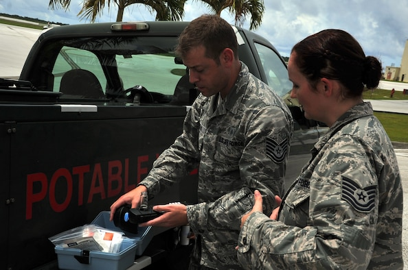 Tech. Sgt. Marcus Poulos, 36th Medical Operations Squadron Bioenvironmental Flight environmental NCO in charge, and Tech. Sgt. Richelle Rodriguez, 36th MDOS ambulance services NCOIC, test the pH level of a water sample taken from a potable water transport truck Aug. 22, 2013, on Andersen Air Force Base, Guam. Eight randomly selected drinking water outlets on base are tested by the bioenvironmental Airmen at least once per month. (U.S. Air Force photo by Staff Sgt. Melissa B. White/Released)