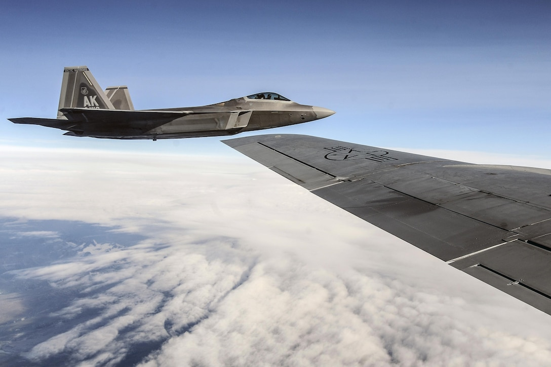 An F-22 Raptor flies alongside a KC-135 Stratotanker during Red Flag-Alaska 13-3 over the Joint Pacific Alaska Range Complex Aug. 14, 2013. Red Flag-Alaska is a series of Pacific Air Forces commander-directed field training exercises for U.S. and partner nation forces, providing combined offensive counter-air, interdiction, close-air support, and large force employment training in a simulated combat environment. (DOD photo/Senior Airman Zachary Perras)