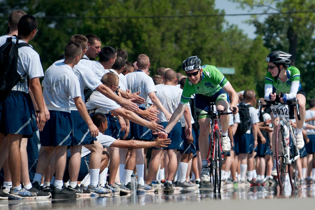 "A Hotter'N Hell Hundred rider greets Airmen in training at Sheppard Air Force Base, Texas, on his way out of the base Aug. 24, 2013. After ""Airpower Alley"" and a rest stop, bicycle riders rode through a gauntlet of hundreds of Airmen screaming and cheering them on to the finish line. As part of the event, hundreds of Sheppard AFB volunteers helped riders needing a break at the last rest stop before the finish line. Across all the rest stops, riders consumed more than 20,000 bananas, more than 9,000 oranges, more than 8,000 pickles, 2,800 gallons of PowerAde and 10,000 gallons of water. The annual race is in its 32nd year and celebrates the founding members of Texoma with a 100-mile race in 100-degree temperatures. (U.S. Air Force photo/Staff Sgt. Mike Meares)"