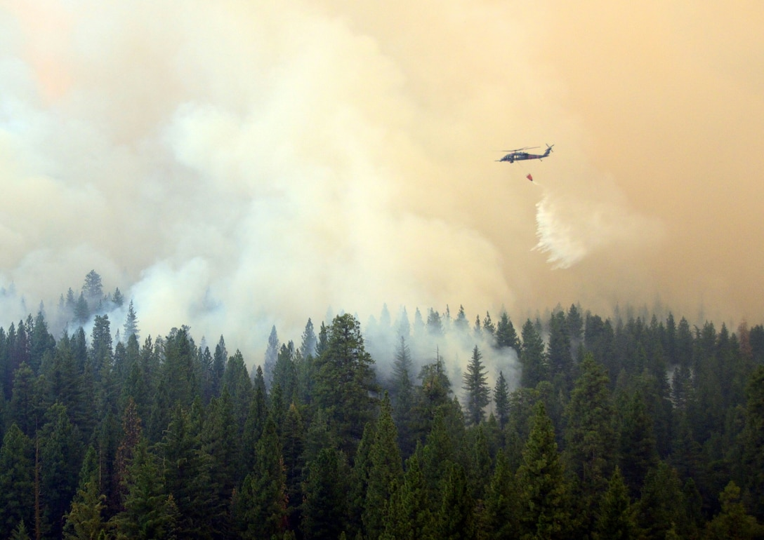 California Air National guardsmen from the 129th Rescue Wing perform precision water bucket drops Aug. 26, 2013, in support of the Rim Fire suppression operation at Tuolumne County near Yosemite, Calif. (Courtesy photo/Staff Sgt. Ed Drew)