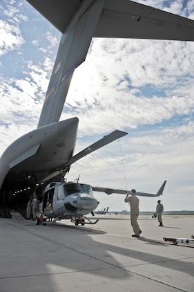 Marine Light Attack Helicopter Squadron 773 Marines and 305th Aerial Port Squadron members load a UH-1N Huey onto a C-17 Globemaster III Aug. 19, 2013, at Joint Base McGuire-Dix-Lakehurst, N.J. HMLA-773 is deploying on a Dutch ship alont the west coast of Africa.