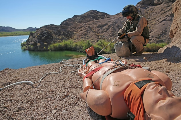 Navy Seaman Curt Hansen, a search and rescue medical technician with Headquarters and Headquarters Squadron and a native of Burlington, Ky., goes over proper harnessing procedures before being lifted up into the air by a SAR UH-1N Huey helicopter during a routine training exercise conducted at Ledge on the River, just northeast of Marine Corps Air Station Yuma, Ariz.,Thursday.