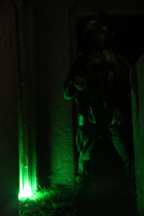A Marine serving with Alpha Company, 1st Reconnaissance Battalion, posts security outside a cleared compound during a mission rehearsal exercise here, Aug. 19, 2013. During the exercise, Marines performed a night raid on a military operation in urban terrain town and detained possible enemy combatant role-players. The MRX assessed the Marines' ability to execute their mission and coordinate logistics with their command element as they prepare to deploy with the 11th Marine Expeditionary Unit next year.