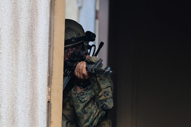 A Marine serving with Alpha Company, 1st Reconnaissance Battalion, responds to simulated small-arms fire during a mission rehearsal exercise here, Aug. 20, 2013. During the exercise, Marines performed a night raid on a military operations in urban terrain town and detained possible enemy combatants. The MRX assessed the Marines' ability to execute their mission and coordinate logistics with their command element as they prepare to deploy with the 11th Marine Expeditionary Unit next year.