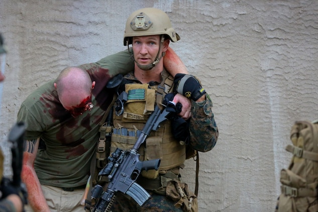 A Marine serving with 1st Reconnaissance Battalion helps a simulated hostage to safety after clearing the house he was held in by enemy combatants during a mission rehearsal exercise here, Aug. 20, 2013. Marines responded to simulated small-arms fire and artillery rounds with suppressing fire and patrols through the area. An evaluator followed each squad of Marines and assessed their various skills including tactics, coordination and execution during the mission.