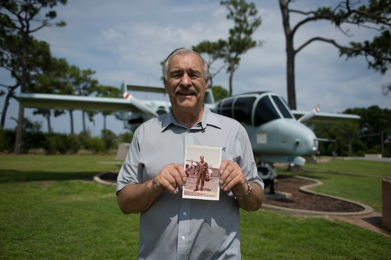 Kenneth Krohn, a local business owner and former Air Force pilot, poses in front of the exact aircraft he flew during the Vietnam War while holding a picture of himself posing in front of the same aircraft at the air park on Hurlburt Field, Fla., Aug. 12, 2013.  Krohn primarily flew the OV-10 Bronco during the Vietnam War, mainly performing reconnaissance missions. (U.S. Air Force photo/ Senior Airman Hayden Hyatt)