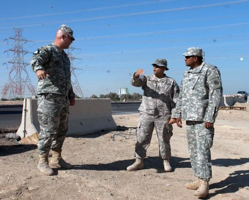 Master Sgt. Steve Kirby, force protection NCO for ASG Kuwait, left, 1st Lt. Teofilo Espinal, Base Defense Liaison Team (BDLT) officer-in-charge, center, and Staff Sgt. Miguel Santiago plan the placement of concrete barriers just outside the camp here in October.