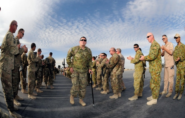 U.S. Army Spc. Lyle Yantz, of Sedalia, Mo., and several other service members participating in Operation Proper Exit are greeted at Kandahar Airfield, Afghanistan, Dec. 6, 2012. Operation Proper Exit brings severely wounded service members back to the theater where they sustained their injuries to provide a firsthand progress update on the continuing mission and to help in the healing process.