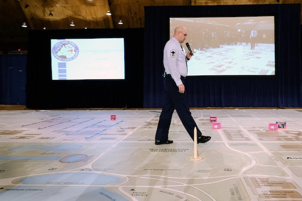 Senior Master Sgt. Scott Hinds, of the District of Columbia Air National Guard, walks along a large-scale map while giving a briefing on the 57th Presidential Inauguration on Dec. 12, 2012.
