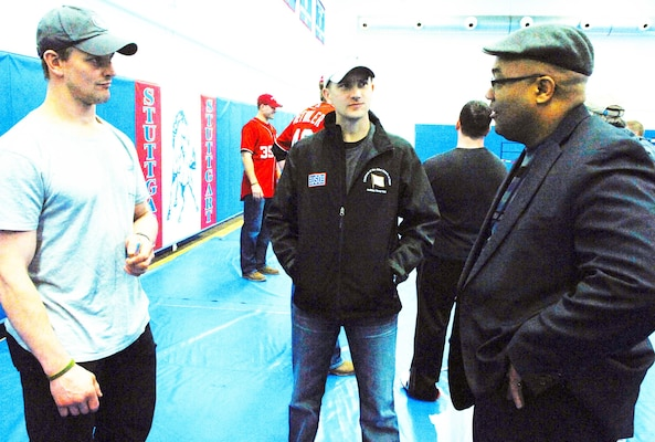 Shane Hudella, center, founder of the non-profit organization Defending the Blue Line, which donates hockey equipment to military families, chats with Matt Hendricks, left, a National Hockey League player with the Washington Capitals, and a local hockey fan before a United Service Organizations show at Patch Barracks in Stuttgart, Germany, Dec. 17, 2012.