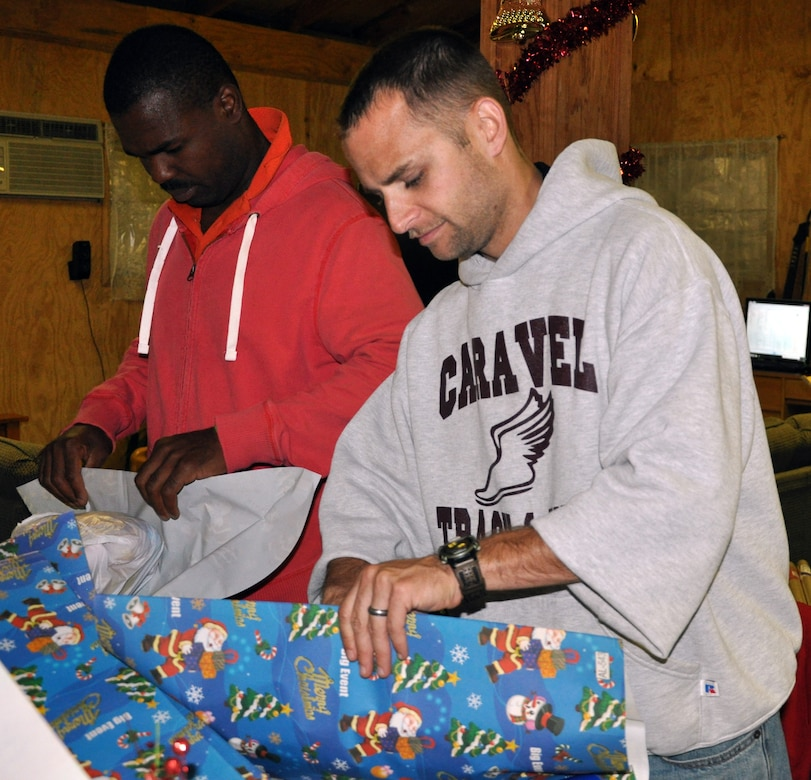 U.S. Army Capt. Jelani Berry and U.S. Air Force Capt. Michael Quashne wrap holiday gifts to be given to local orphans during a gift wrapping party held at Soto Cano Air Base, Honduras, Nov. 30, 2013.  More than 100 volunteers from Joint Task Force-Bravo participated in the event and wrapped more than 300 gifts to be given to the children.  (U.S. Air Force photo by Capt. Zach Anderson)