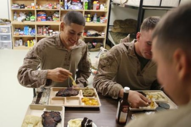 Lance Cpl. Salvador Nunez, a squad automatic rifleman serving with 3rd Battalion, 7th Marine Regiment's Security Force Assistance Advisor Team, smiles as he eats during his squad's Thanksgiving dinner here, Nov. 28. Nunez, 21, from Aurora, Ill., was the first Marine to share what he was grateful for on Thanksgiving. Nunez said it was hard being away from his family, but at least he got to spend time with his brothers.