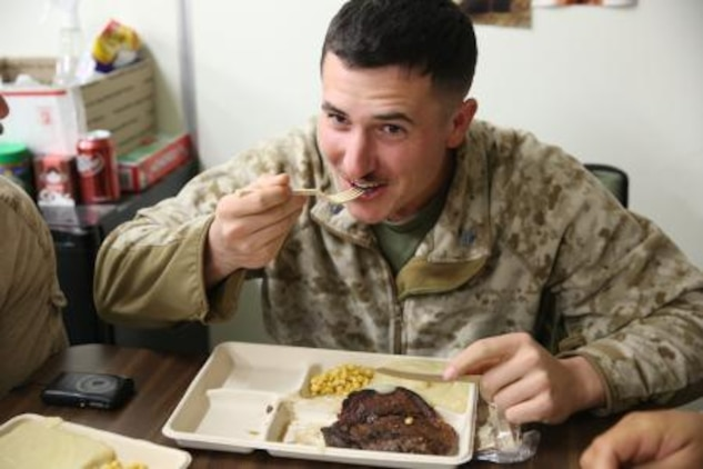 Cpl. Alex Martinez, an assistant patrol leader serving with 3rd Battalion, 7th Marine Regiment's Security Force Assistance Advisor Team, smiles while he enjoys a piece of steak during his squad's Thanksgiving dinner here, Nov. 28. Martinez, a 22-year-old native from Arcata, Calif., decided to have the Marines in his squad enjoy a Thanksgiving meal together, since they could not spend Thanksgiving with their actual family.
