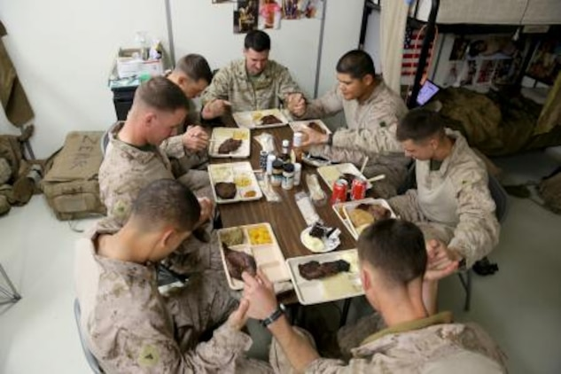 Marines serving with 3rd Battalion, 7th Marine Regiment's Security Force Assistance Advisor Team, pray before their Thanksgiving dinner here, Nov. 28. The Marines used the holiday meal as a time to share their family traditions with one another.