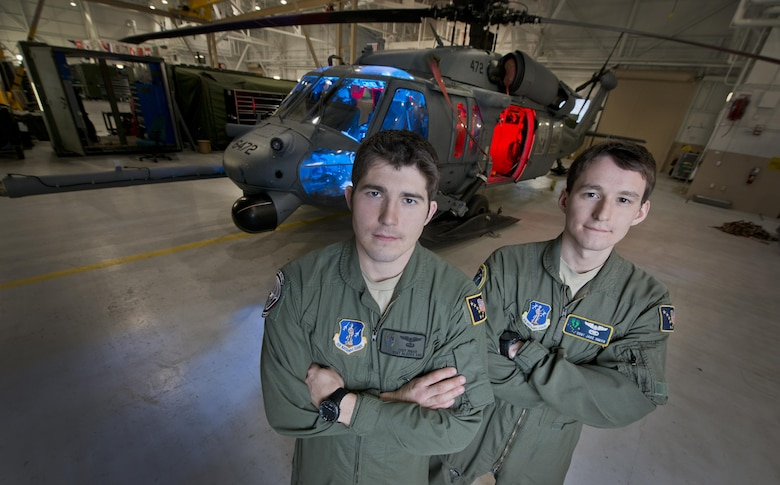 Pararescue Jumper Staff Sgt. Cody Inman, assigned to the 210th Rescue Squadron, Alaska Air  National Guard, left and his brother Special Mission Aviator Staff Sgt. Jacob Inman, assigned to the 212th Rescue Squadron, Alaska Air National Guard, pose for a photograph in front of a HH-60 Pave Hawk helicopter on Joint Base Elmendorf-Richardson, Alaska, Nov. 20, 2013.