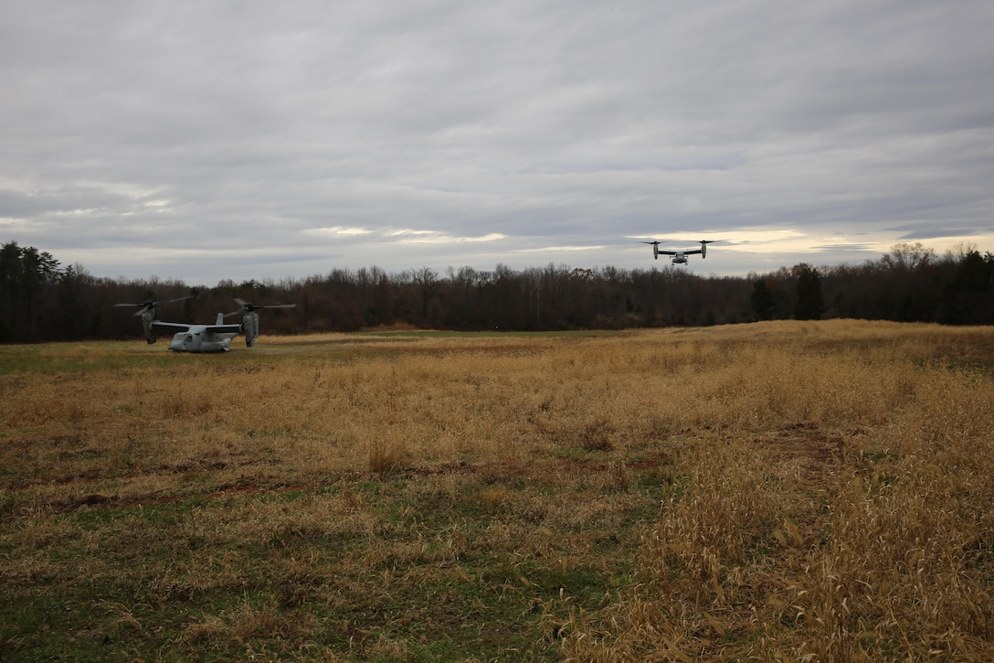An MV-22 Osprey waits for Marines who are coming from a second Osprey after recovering a downed aircraft during a Tactical Recovery of Aircraft and Personnel mission aboard Marine Corps Base Camp Upshur, Va., November 26. The mission was a scenario during the battalions Alternate Mission Rehearsal exercise in preparation for an upcoming deployment.