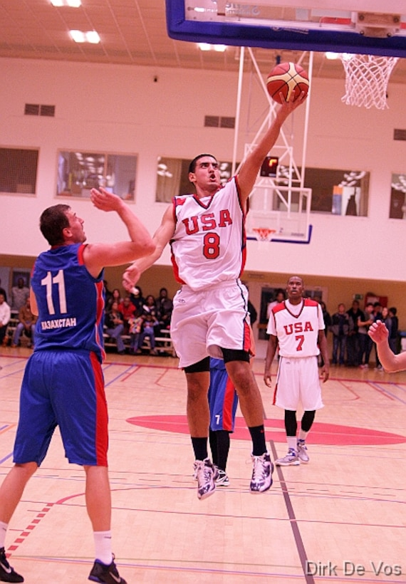 Navy LTJG Romeo Garcia scores over his opponent from Kazakhstan during the 2013 SHAPE International Basketball Tournament held at SHAPE (Mons), Belgium 24-30 November.  USA defeats Kazakhstan 104-55.