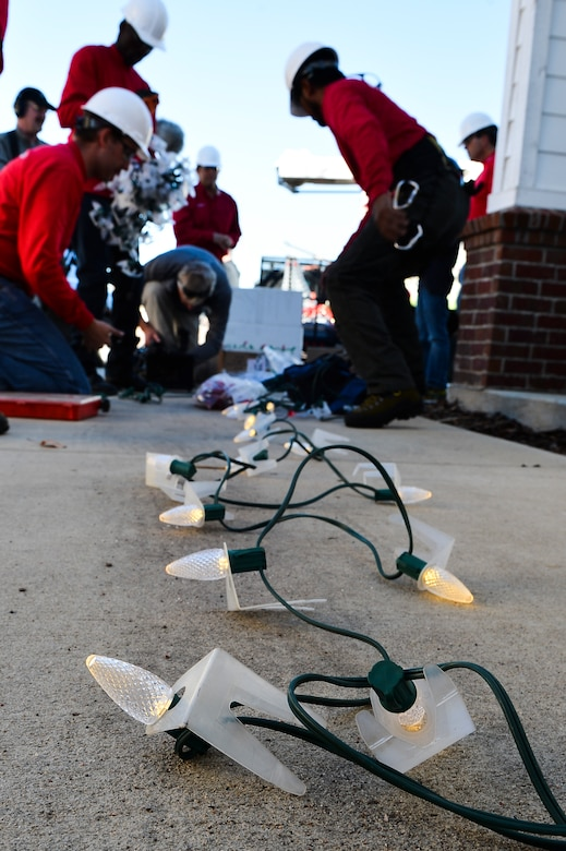 Christmas Decor by Swingle Lawn, Tree & Landscape Care decorators assemble Christmas lights Nov. 29, 2013, in family housing on Buckley Air Force Base, Colo. Maj. Matthew Anderson, 460th Civil Engineer Squadron, and his family applied and were selected for the Decorated Family Program which provided lights, wreaths other ornaments applied by a professional decorating team to military members and families. (U.S. Air Force photo by Senior Airman Riley Johnson/Released)