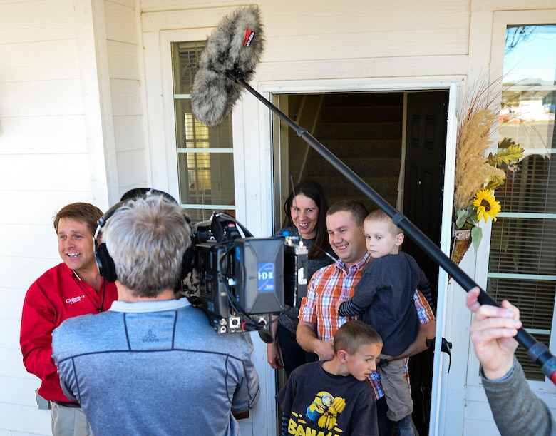 Christmas Decor by Swingle Lawn, Tree & Landscape Care decorators and an NBC camera crew surprise Maj. Matthew Anderson, 460th Civil Engineer Squadron, and his family Nov. 29, 2013, in family housing on Buckley Air Force Base, Colo. The Andersons applied and were selected for the Decorated Family Program, which provided lights, wreaths and other ornaments applied by a professional decorating team to military members and families. (U.S. Air Force photo by Senior Airman Riley Johnson/Released)