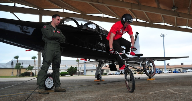 "Tom ""Fuzzy"" Hall, professional BMX rider, performs a ""Tail Whip"" in front of a T-38 Talon, as his brother-in-law, Lt. Col. Joe Granducci, 325th Training Support Squadron assistant director of operations, looks on. (U.S. Air Force photo by Airman 1st Class Dustin Mullen)"