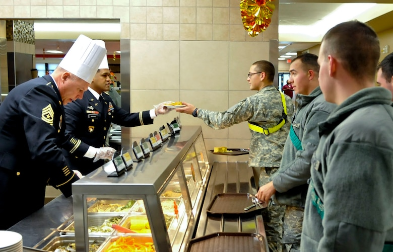 From left, U.S. Army Sgt. Maj. William Platt, 128th Aviation Brigade sergeant major, and Lt. Col. Benjamin Bahoque, 128th Avn. Bde. deputy commanding officer, serve Soldiers a Thanksgiving meal at Fort Eustis, Va., Nov. 28, 2013. As part of a continued tradition, members of Fort Eustis' leadership serve holiday meals to Soldiers who are unable to go home for the holidays. (U.S. Air Force photo by Staff Sgt. Wesley Farnsworth/Released)