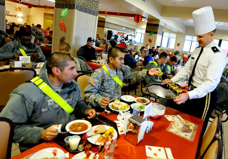U.S. Army Brig. Gen. Christopher Mcpadden, right, U.S. Army Capability Requirements and Integration Command director of concept development and learning, serves glasses of sparkling juice to Soldiers during a Thanksgiving dinner at Fort Eustis, Va., Nov. 28, 2013.  As part of a continued tradition, Fort Eustis' leadership serves holiday meals to Soldiers who are unable to go home for the holidays. (U.S. Air Force photo by Staff Sgt. Wesley Farnsworth/Released)