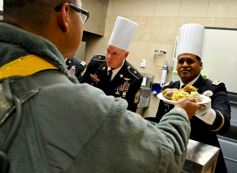 U.S. Army Lt. Col. Benjamin Bahoque, 128th Aviation Brigade deputy commanding officer, serves a Soldier a Thanksgiving meal at the Resolute Cafe at Fort Eustis, Va., Nov. 28, 2013. Bahoque was one of many members of Fort Eustis' leadership who served a meal to Soldiers who were unable to go to home for the holiday. (U.S. Air Force photo by Staff Sgt. Wesley Farnsworth/Released)