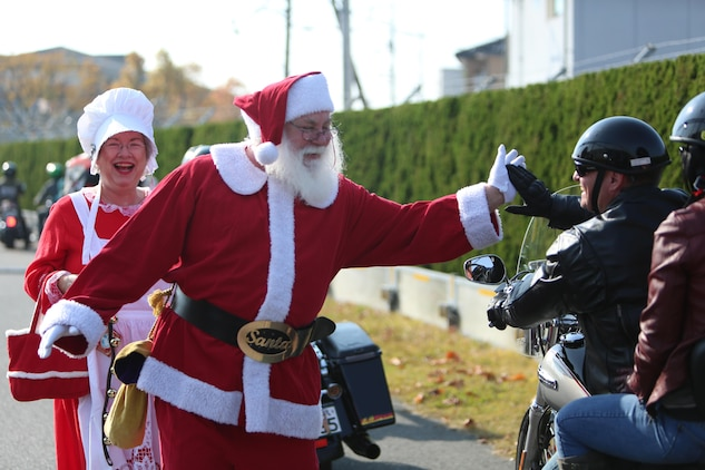 Mr. and Mrs. Claus, portrayed by John and Jan Jenson, walk down the road and high-five a motorcycle rider during the Motorcycle Rally and Toy Drive event hosted by the Marine Thrift Store aboard Marine Corps Air Station Iwakuni, Japan, Nov. 24, 2013. Mr. and Mrs. Claus helped collect the donated toys from the event, as well as walked down the road to greet the riders and gave a little 'ho ho ho' Christmas spirit encouragement.