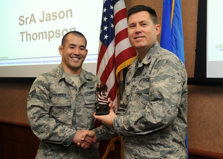 Senior Airman Jason Thompson, 460th Operations Group data systems operator, receives the 460th Space Wing Airman of the Month Award for November from Col. Dan Wright, 460th SW commander, Dec. 3, 2013, at Buckley Air Force Base, Colo. Thompson received the award for his exceptional service in executing the space wing's first Management Internal Control Toolset deficiency capability, building five checklists for 34 errors. Thompson also inspected 25 individual qualification folders identifying one critical systemic fault and averting a critical readiness crisis which was key to the groups Air Force Inspection System. (U.S. Air Force photo by Senior Airman Marcy Copeland/Released)