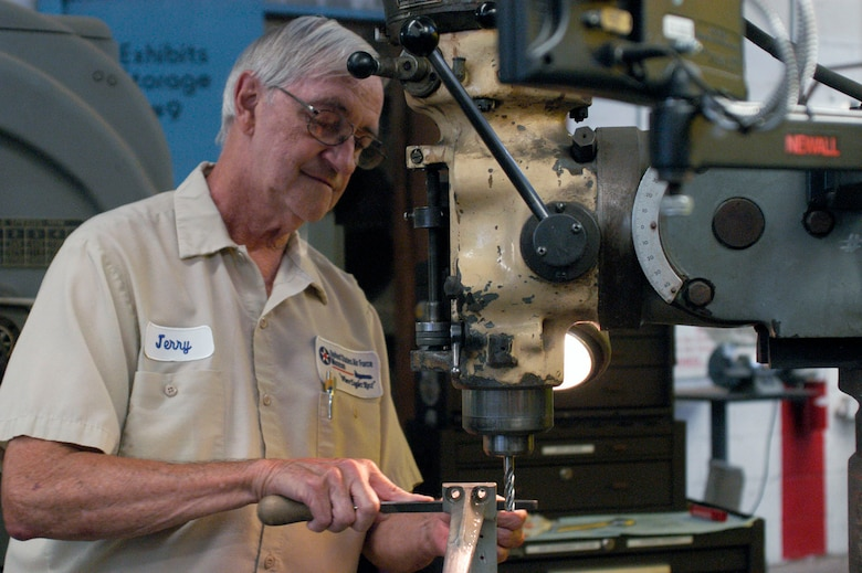 """DAYTON, Ohio -- Jerry Archer, a volunteer machinist in the Restoration Division, works on a small part for the B-17F """"Memphis Belle."""" (U.S. Air Force photo)"""